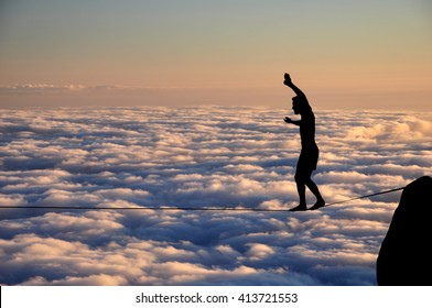 Silhouette of young man balancing on slackline high above clouds. Slackliner balancing on tightrope beautiful colorful sky and clouds behind, highline silhouette.