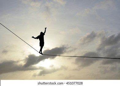 Silhouette of young man balancing on slackline, sun, beautiful colorful sky and clouds behind. Slackliner balancing on tightrope between two rocks, highline silhouette.