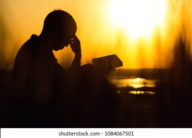 silhouette of a young man with a Bible in his hands in the field, male praying to God iwith remorse and gratitude in nature, faith in difficulties of life, the concept of religion and spirituality
