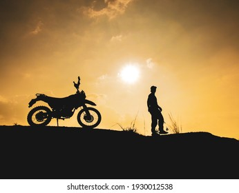 Silhouette of young man biker and a motorcycle on the off-road with sunset light background