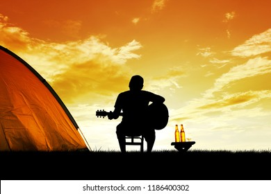 Silhouette of young man camping and strum a guitar instrumental music to relax against the background of sunset - Wilderness Travel lifestyle and Friendship concept.