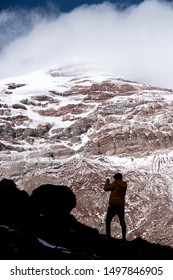 Silhouette of young man contemplating the majesty of nature, an unforgettable vacation at the Chimborazo volcano in Ecuador