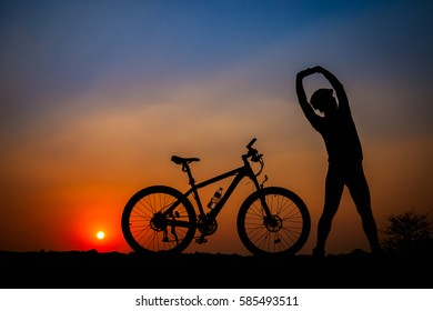 Silhouette of young man cyclist on sunset.