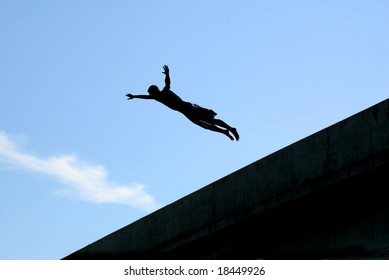 A silhouette of a young man diving from a bridge.