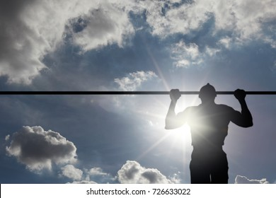 Silhouette of a young man doing pull-up exercise on a horizontal bar against a blue cloudy sky with sun flare.