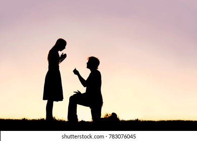 A silhouette of a young man, down on one knee and holding a diamond engagement ring, proposing to his girlfriend.