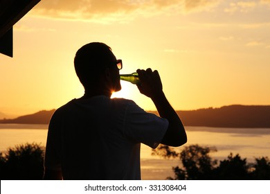 Silhouette of a young man drinking beer out of a glass bottle at sunset