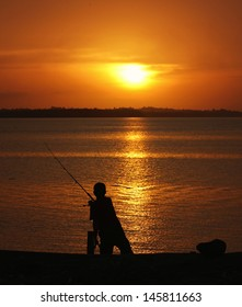 a silhouette of a young man fishing