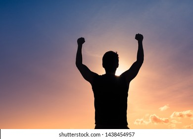 Silhouette of young man with fist in the air, Victory and winning concept.