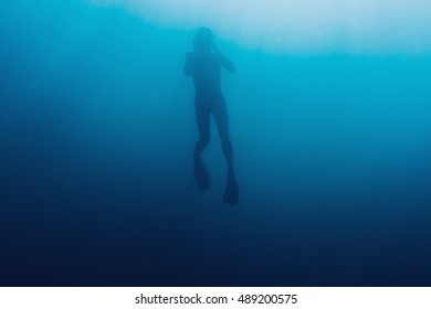 Silhouette of young man free diver swimming underwater in blue deep sea