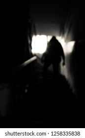 Silhouette of a young man going up the stairs to the light.Man walkin upstairs in blur in black and white.