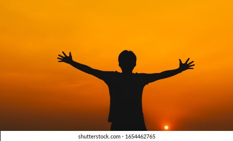 Silhouette young man with hands raised standing high up during sunset background