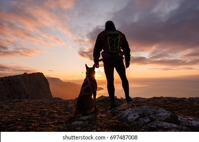 Silhouette of young man with his dog at dawn with sea and mountain on background.