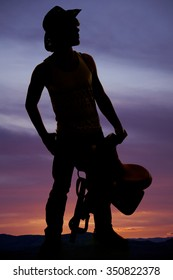 A silhouette of a young man in his western hat, holding on to his saddle.