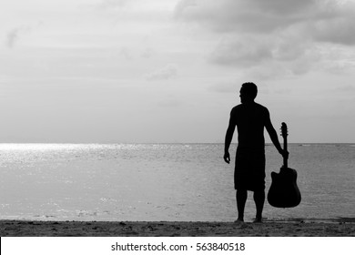 Silhouette of young man holding his guitar while standing up looking out to the sea at sunset in the island of Koh Phangan, Thailand. Music artist finding inspiration. Black and white photography