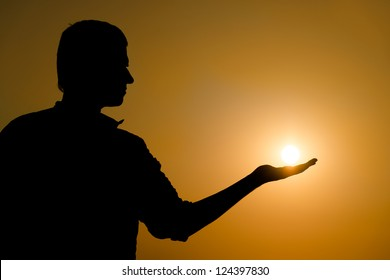 Silhouette of young man holding the sun on his hand at yellow sunset background