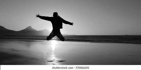 Silhouette of an young man jumping on the beach at Cape Town city, South Africa. Black and white picture.
