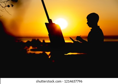 silhouette of a young man painting a picture with paint brush and palette on linen on an easel outdoors, painter face profile engaged in art on nature in a field at sunset