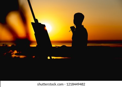 silhouette of a young man painting a picture with paints on canvas on an easel outdoors, boy with paint brush and palette engaged in art on nature in a field at sunset