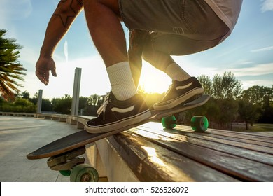 Silhouette of young man performing with skateboard up wood bench at sunset in urban city park - Skater having fun with back sunlight - Extreme sport concept - Focus on left shoe - Warm filter