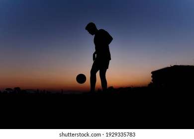 Silhouette of young man playing soccer on the beach with a ball at sunset