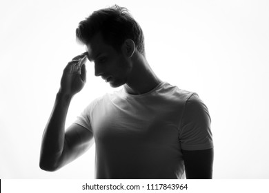 Silhouette of young man portrait in shirt with hand on studio isolated white background. Close up.