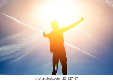 Silhouette of young man rejoicing achievement raised the hands, person has attained the goal, concept victory over self, silhouette man exploded to the top hill