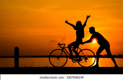 Silhouette of young man riding a bicycle on the sunset