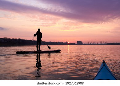 Silhouette of a young man rowing on a SUP during a beautiful winter sunrise on the river