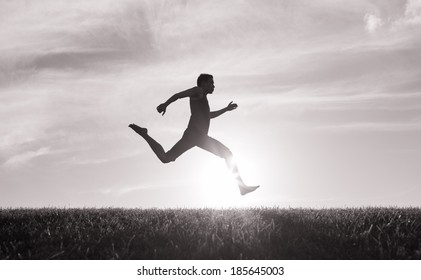 Silhouette of young man running.