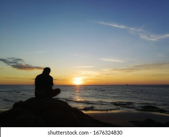 silhouette of young man sitting on the rock and watching the sunset at the seaside