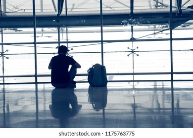 The silhouette of a young man sitting and waiting for flight in Airport view at the airport.traveling concept.