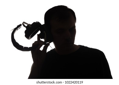 Silhouette of young man with a smartphone listening to music with big headphones old