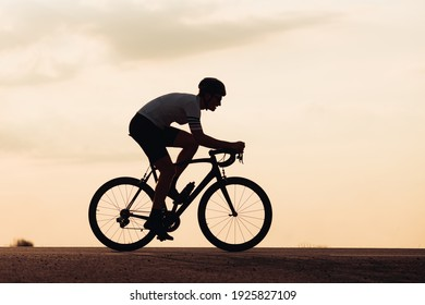 Silhouette of young man in sport outfit and helmet riding bike on paved road during sunset. Active cyclist training everyday on fresh air to keep shape.