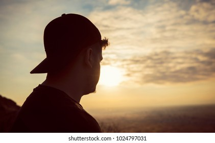 Silhouette of young man, standing alone, lonly by the sunset light