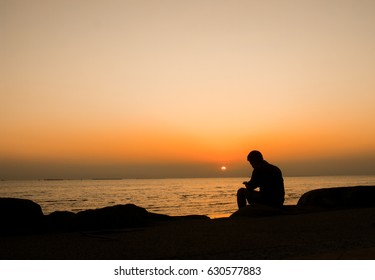 Silhouette of young man, standing alone, lonly by the sunset light of sea