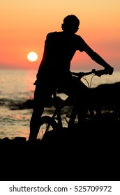 Silhouette of a young man standing with bicycle on a sea coast and looking at the sunset