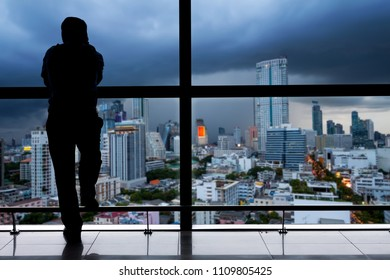 Silhouette of young man standing near the window on skyscraper and looking to the city under cloudy rain