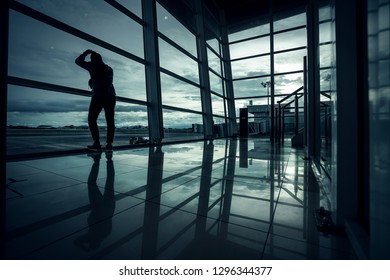 Silhouette young man is standing near window at the airport and watching plane before departure