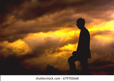 Silhouette of young man standing.on sunset.