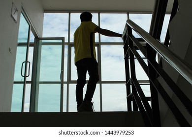 The silhouette of a young man stands sadly alone on the stairs in a low light, shooting blurred images