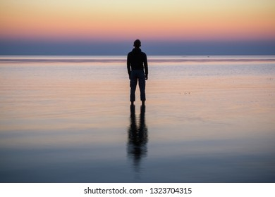 Silhouette of young man staying in the calm water of the sea. Sunset.