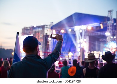 silhouette of young man; taking photo rock concert on the phone, open fest