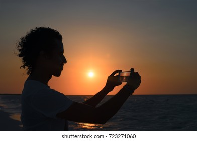 Silhouette of young man taking photo of sunset at seaside with his smartphone