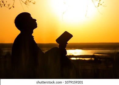 silhouette of young man turns to God with questions about life sitting under tree on the lawn, male on the nature looking up at the sky with fatigue and the hope, the concept of faith and spirituality