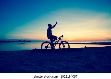 silhouette of young man, woman cyclist on sunset sky with cloud