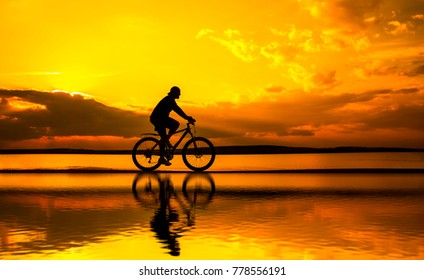 silhouette of young man woman cyclist on sunset sky with clouds Sun on water texture with ripples ride along seashore summer beach at yellow evening horizon sea yellow sunset heaven background.Outdoor