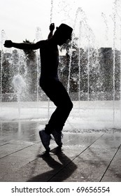 silhouette of young Michael Jackson impersonator dancing in a fountain
