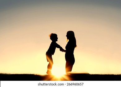 Silhouette of a young mother lovingly holding hands with her happy little child outside in front of a sunset in the sky.