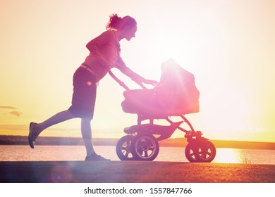 silhouette of a young mother takes care of the baby in a stroller at sunset
